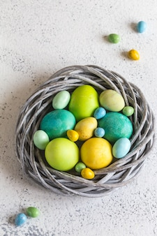 Colorful easter eggs in a nest on a light background.
