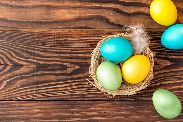 Colorful easter eggs in the nest and nearby on rural wood