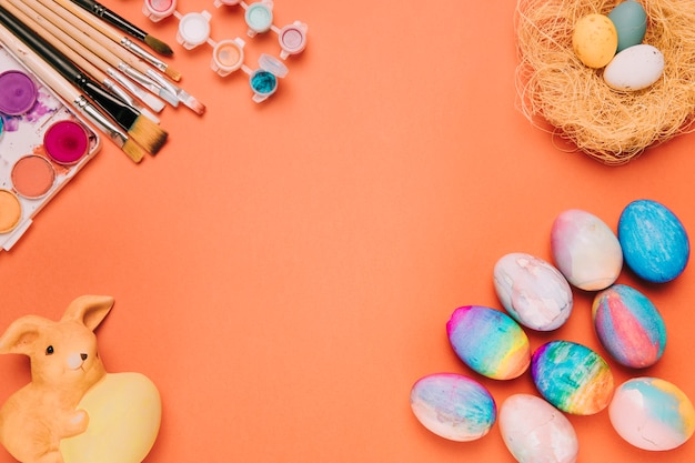 Colorful easter eggs; nest; paint brushes; paint water color box and rabbit statue against orange backdrop