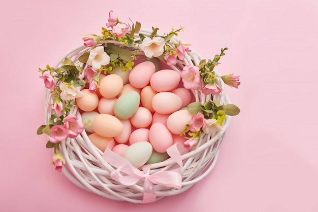 Colorful easter eggs in nest on pastel color background with flowers.