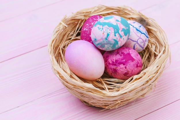 Colorful easter eggs in a nest on pink wooden surface