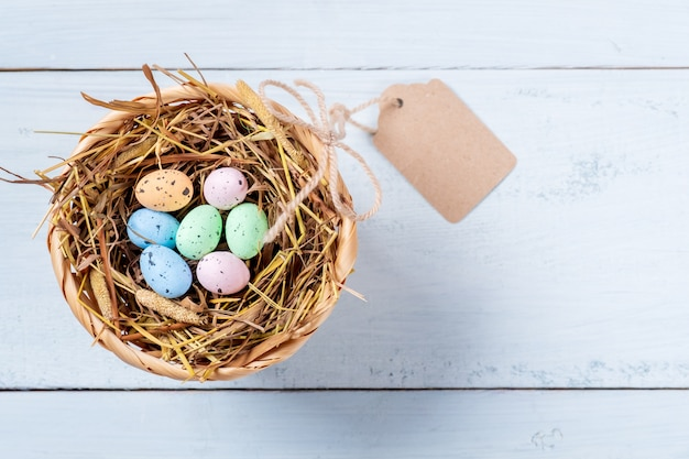 Colorful easter eggs in nest of straw with tag on blue wooden background