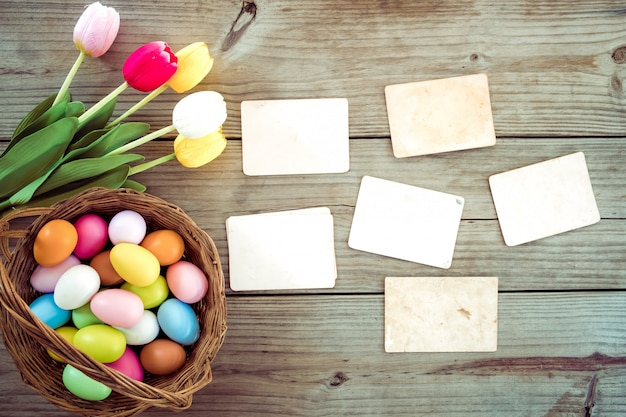 Colorful easter eggs in nest with flower and empty old paper photo album on wood table