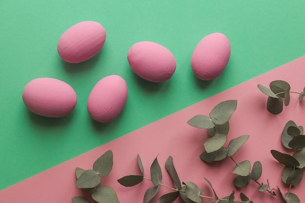 ユーカリの葉と幾何学的なピンクと緑のテーブルにカラフルなイースターエッグ Premium写真