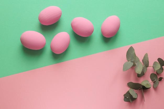 ユーカリの葉と幾何学的なピンクと緑のテクスチャのカラフルなイースターエッグ