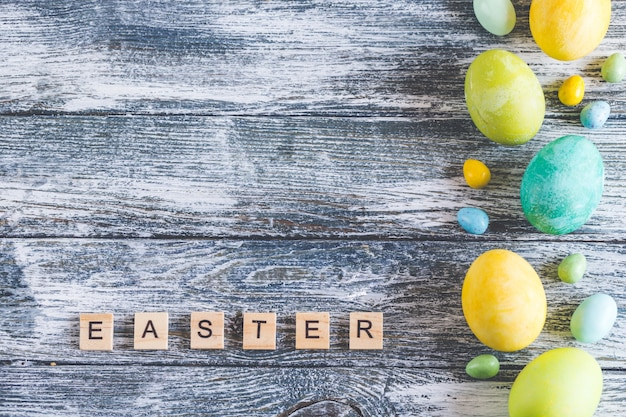 ぼろぼろの青い木製の背景と「イースター」の文字にカラフルなイースターエッグ