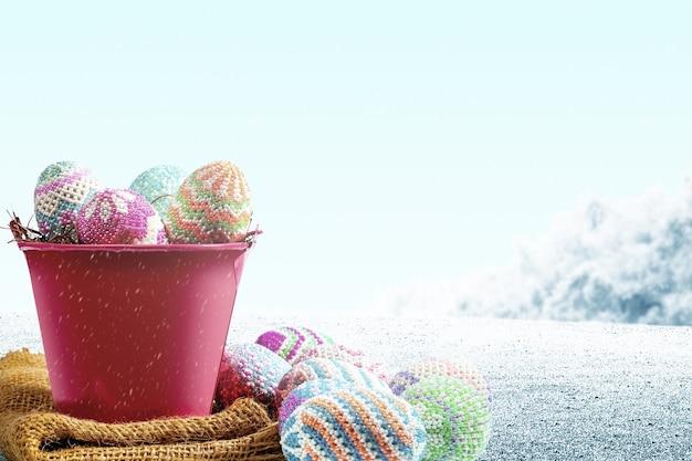 필드에 패브릭과 빨간색 양동이에 둥지에 다채로운 부활절 달걀. 행복한 부활절