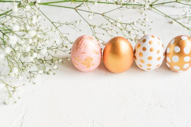 カラフルなイースターエッグがカスミソウの花で飾られた白いコンクリート背景に金、白、ピンク色で連続して描かれました。コピースペースを持つ柔らかい創造的な休日の背景