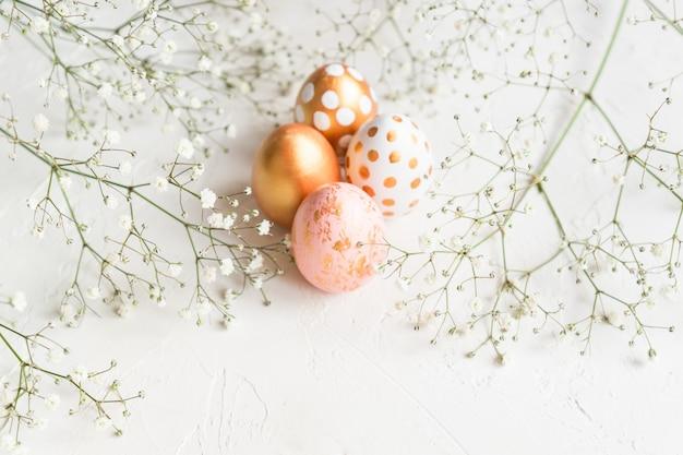 カスミソウの花で飾られた白い背景の金、白、ピンク色で描かれたカラフルなイースターエッグ。コピースペースを持つ柔らかい創造的な休日の背景