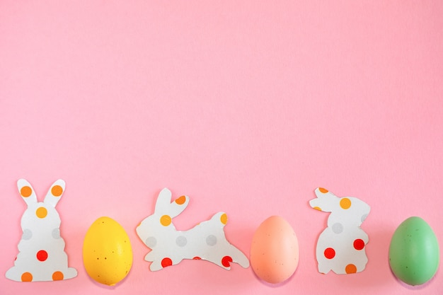Colorful easter eggs and paper silhouettes of an easter bunnys on pink background