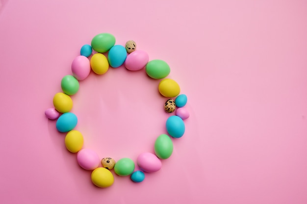 Colorful easter eggs on pink background, top view