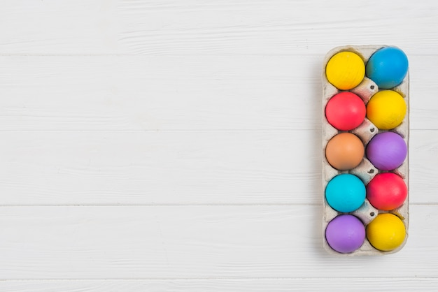 Colorful easter eggs in rack on wooden table