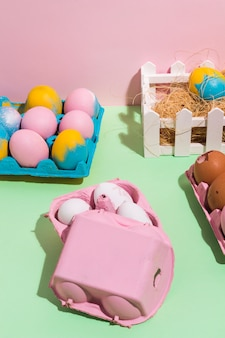 Colorful easter eggs in racks and on hay on table
