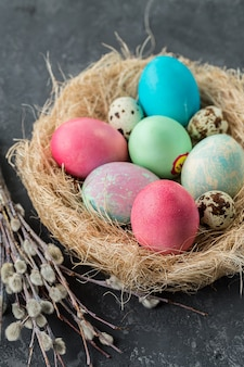Colorful easter eggs in straw nest on a table.