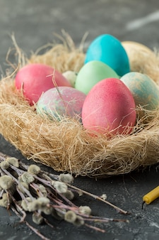 Colorful easter eggs in straw nest on a table