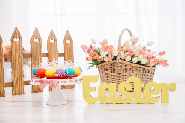 Красочные пасхальные яйца; корзина тюльпанов с желтым пасхальным текстом на деревянном столе