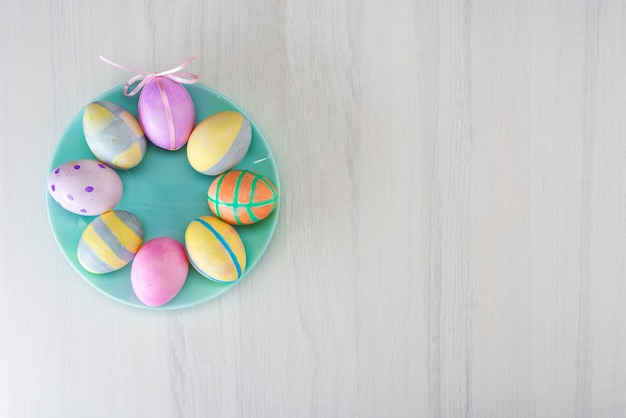 Colorful easter eggs on a turquoise plate on a gray table with place for text, top view