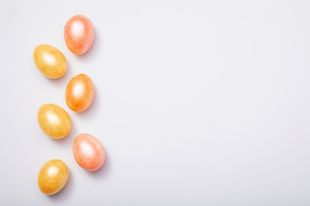 Colorful easter eggs on white background, top view