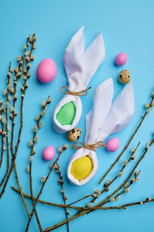 Colorful easter eggs and willow branch on blue background, top view