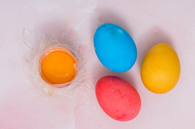 Colorful easter eggs with broken egg in nest