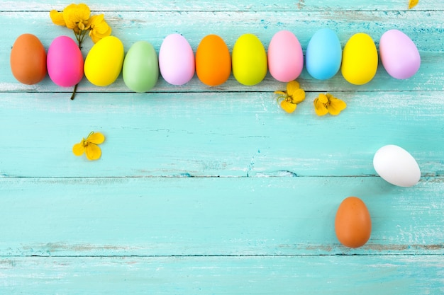 Colorful easter eggs with flower on rustic wooden planks background in blue paint.