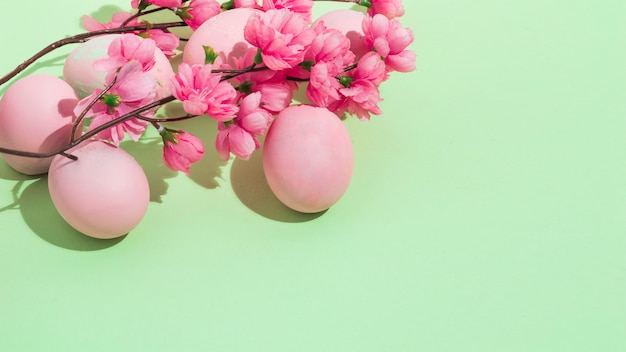 Colorful easter eggs with flowers on green table
