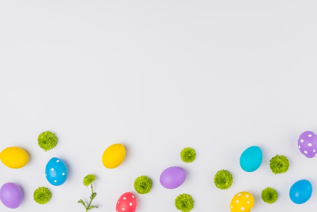 Colorful easter eggs with flowers on table