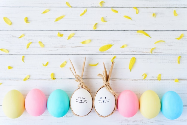 Colorful easter eggs with painted faces and bunny ears in row on a white background