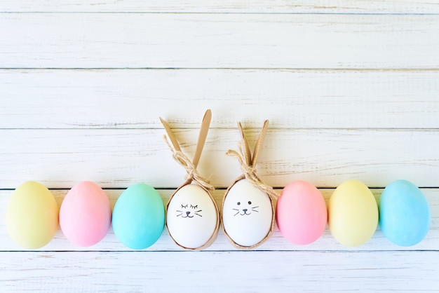 Colorful easter eggs with painted faces and bunny ears in row on white