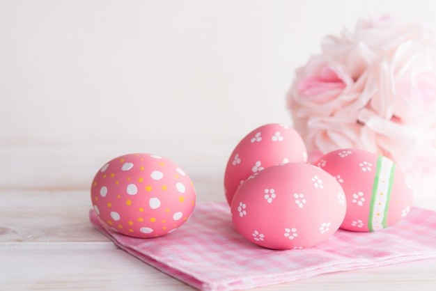 Colorful of easter eggs with pink and white cheesecloth on wooden background.