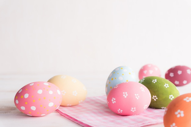 Colorful of easter eggs with pink and white cheesecloth on wooden background