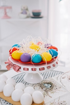 Colorful easter eggs with shredded paper on cakestand over white table