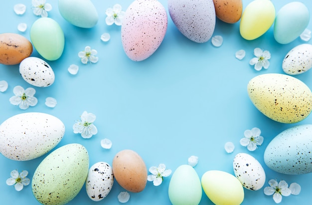 Colorful easter eggs with spring blossom flowers over blue background.