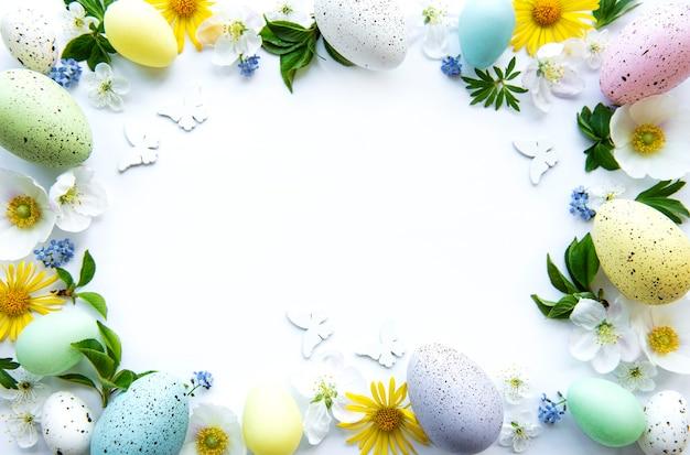 白い背景の上に分離された春の花の花とカラフルなイースターエッグ。