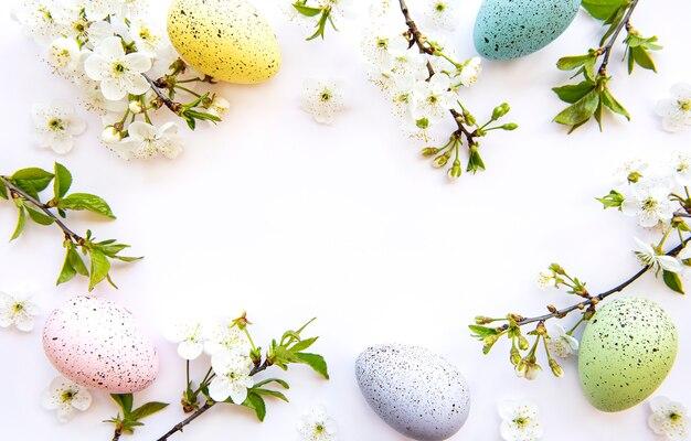 白い表面上に分離された春の花の花とカラフルなイースターエッグ