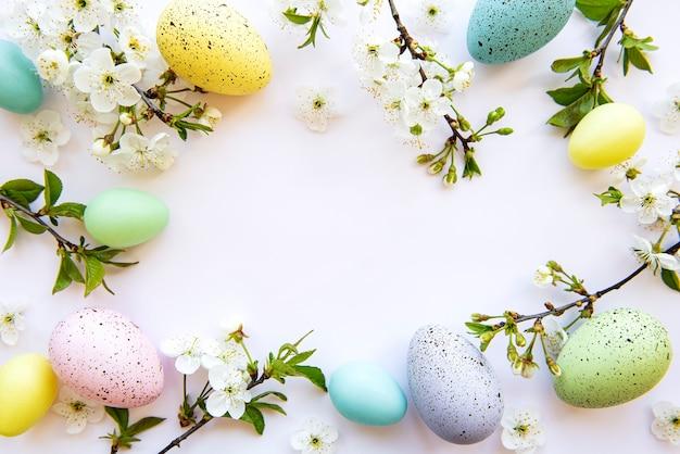 봄 꽃 꽃 화이트 테이블 위에 절연과 다채로운 부활절 달걀. 컬러 계란 휴일 테두리.