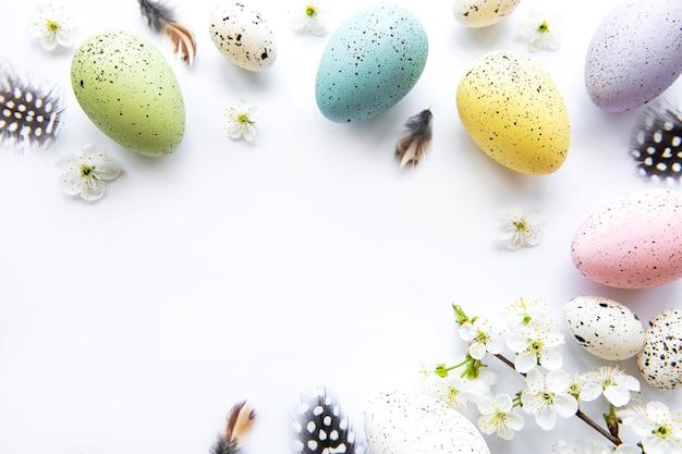 Красочные пасхальные яйца с цветами весеннего цветения изолированные над белым столом. цветные яйца праздник границы.