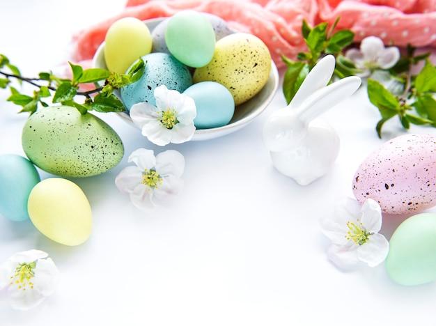 Красочные пасхальные яйца с цветами весеннего цветения изолированные над белым столом.