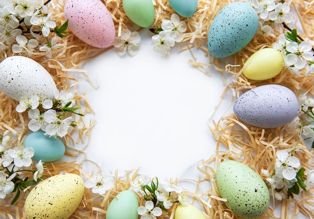 Colorful easter eggs with spring blossom flowers isolated over white background.