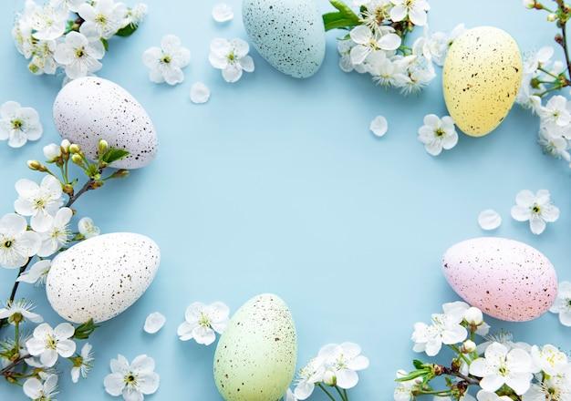 青い表面に春の花の花とカラフルなイースターエッグ