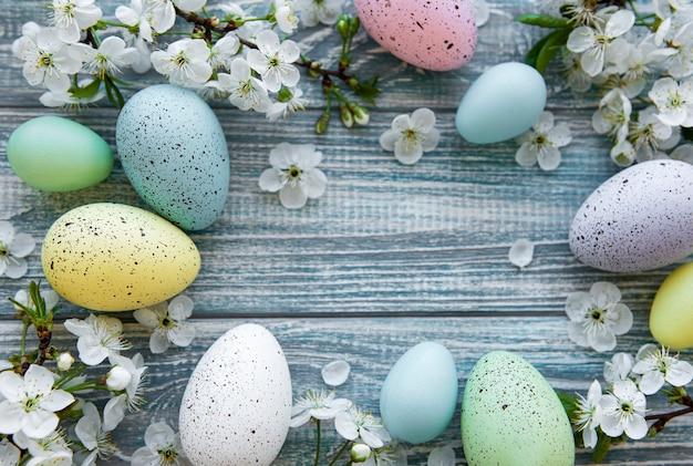 Красочные пасхальные яйца с весенними цветками над голубым деревянным столом. цветные яйца праздник границы.