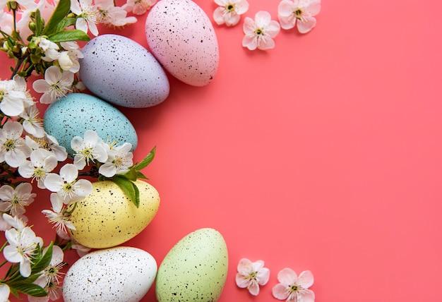 ピンクの背景に春の花の花とカラフルなイースターエッグ。
