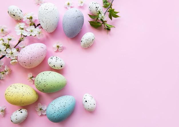 Красочные пасхальные яйца с цветами весеннего цветения над розовым столом. цветные яйца праздник границы.
