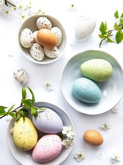 Красочные пасхальные яйца с весенними цветами на белом столе