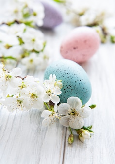 木製の表面に春の花の花とカラフルなイースターエッグ