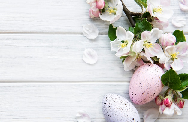 Красочные пасхальные яйца с цветами весеннего цветения над деревянным столом. цветные яйца праздник границы.