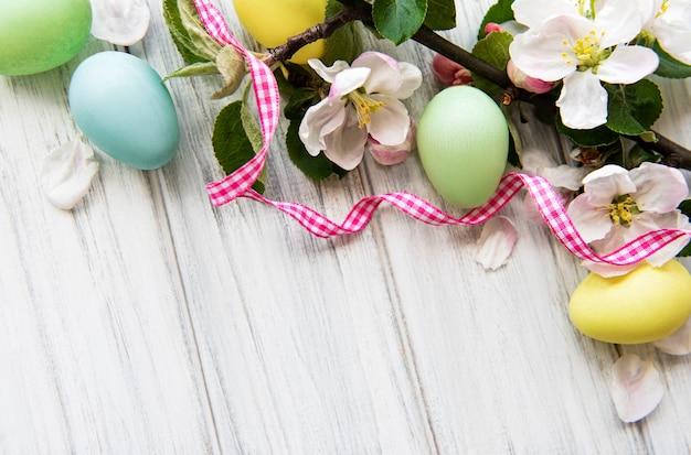 Красочные пасхальные яйца с цветками весеннего цветения над деревянным столом.