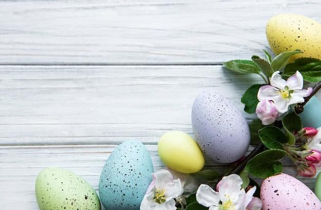 木製のテーブルの上に春の花の花とカラフルなイースターエッグ。