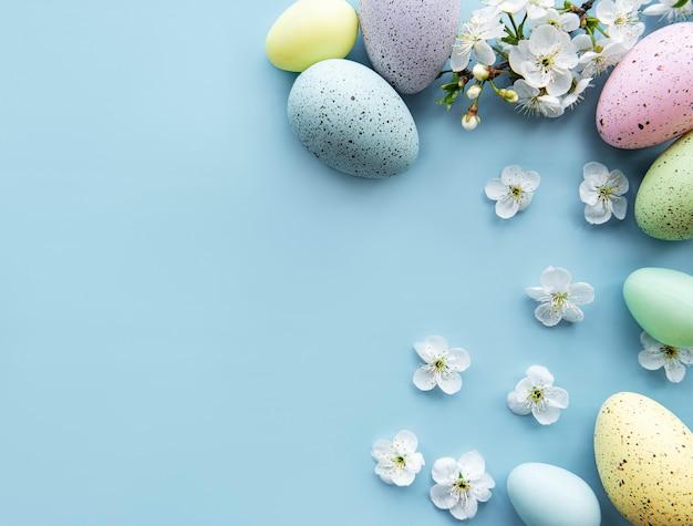 Красочные пасхальные яйца с весенним цветением синим столом. цветные яйца праздник границы.