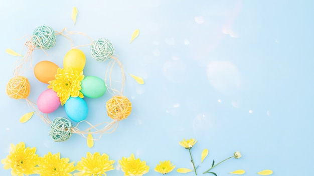 Colorful easter eggs with springtime yellow flowers on a light blue background. flat lay. top view. copy space